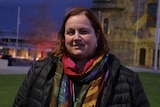 A woman in a coat and scarf stands at a nighttime vigil