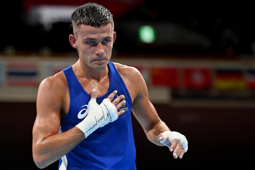 Harry Garside wearing a blue singlet puts his hand on his heart after winning a fight.