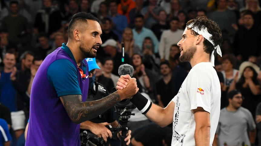Nick Kyrgios and Dominic Thiem clasp hands over the net after their Australian Open tennis match.