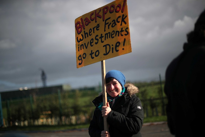 protester holds up a sign reading blackpool where frack investments go to die