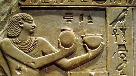 An Egyptian stone carving of a man holding bottles of incense.