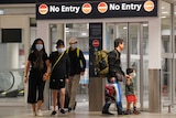 A group of people including men, women and small children with face masks on walking in an airport.