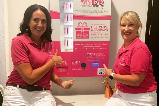 Two women wearing pink t-shirts smile in front of a period pack vending machine