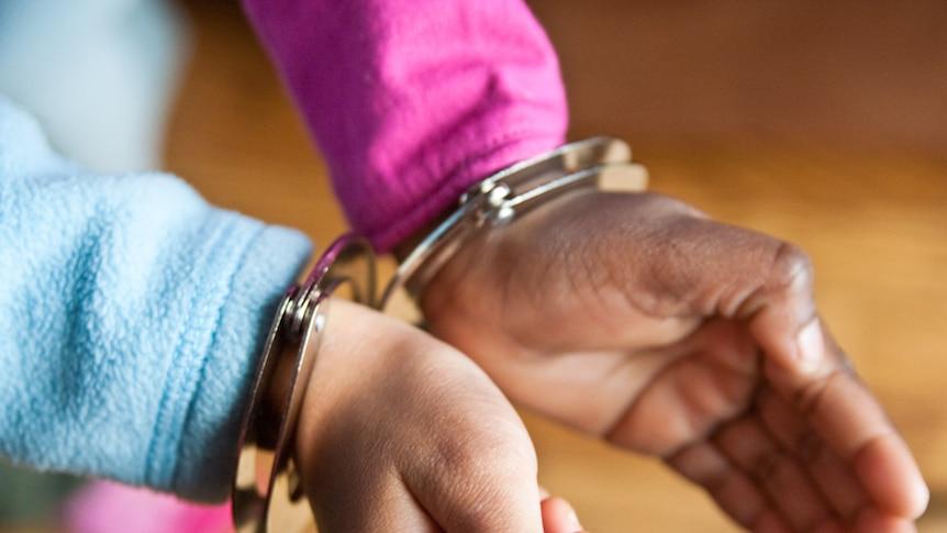 An unidentified child wearing handcuffs