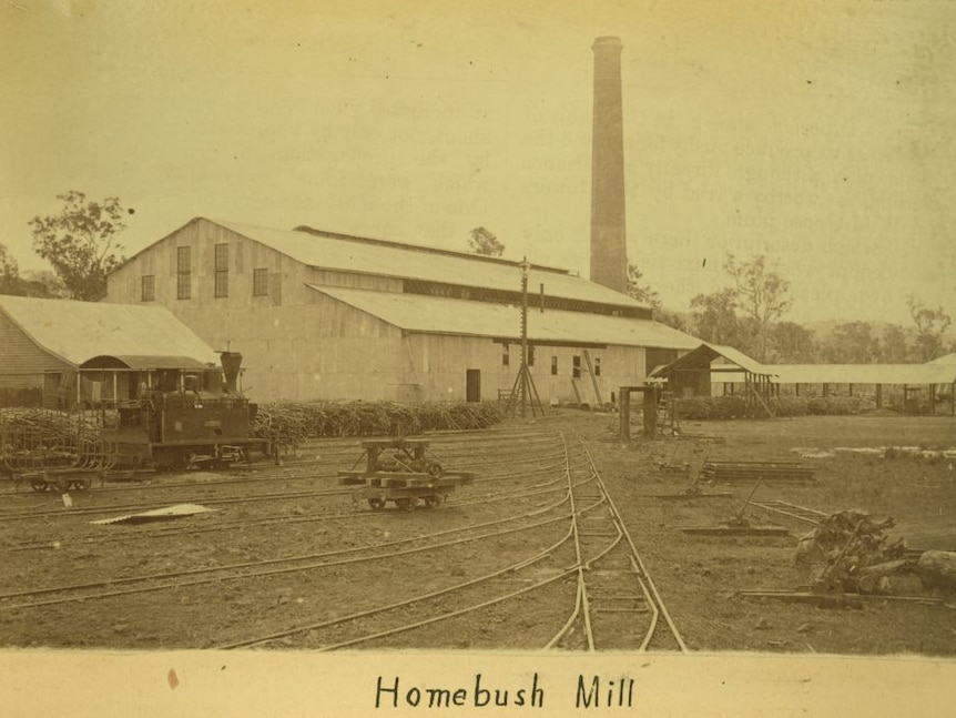 an old image taken of a mill, with a tall chimney stack in the background