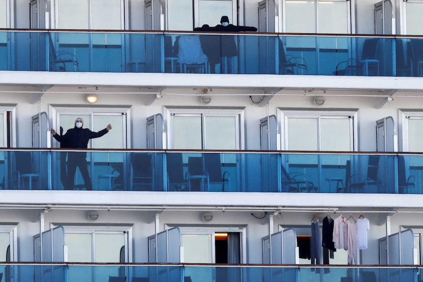 A few passengers on balconies on a cruise ship