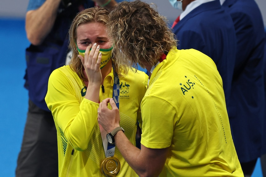A crying Ariarne TItmus is consoled by Dean Boxall. A gold medal is around her neck