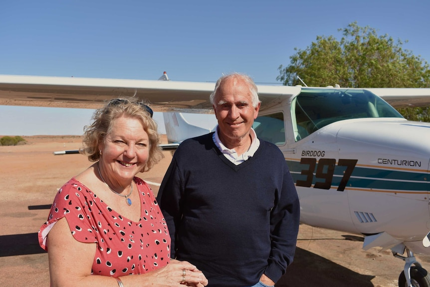 An older couple stand in front of a plane.  Both are smiling and looking at the camera.