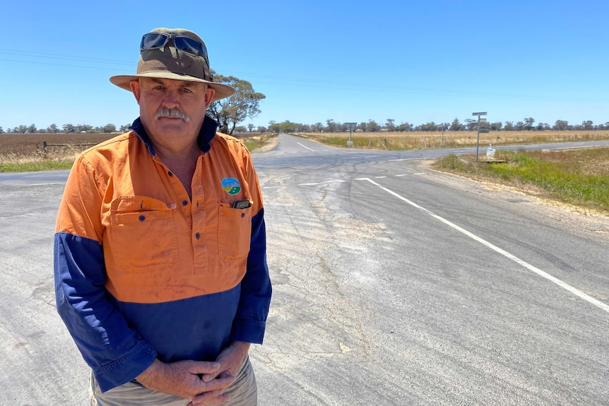 Man in hi vis shirt stands at a country intersection.