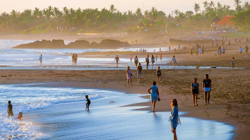 Orang-orang di pantai di Bali saat matahari terbenam