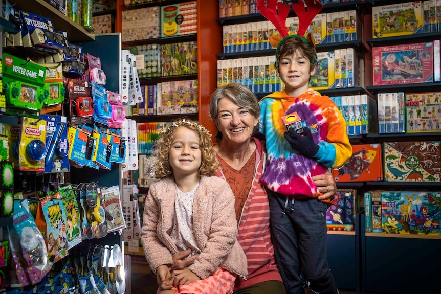 A grandmother sits next to her two grandchildren in a toy shop