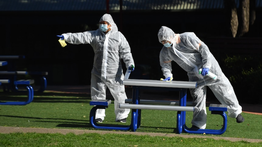 Two people in full PPE clean a table at school grounds