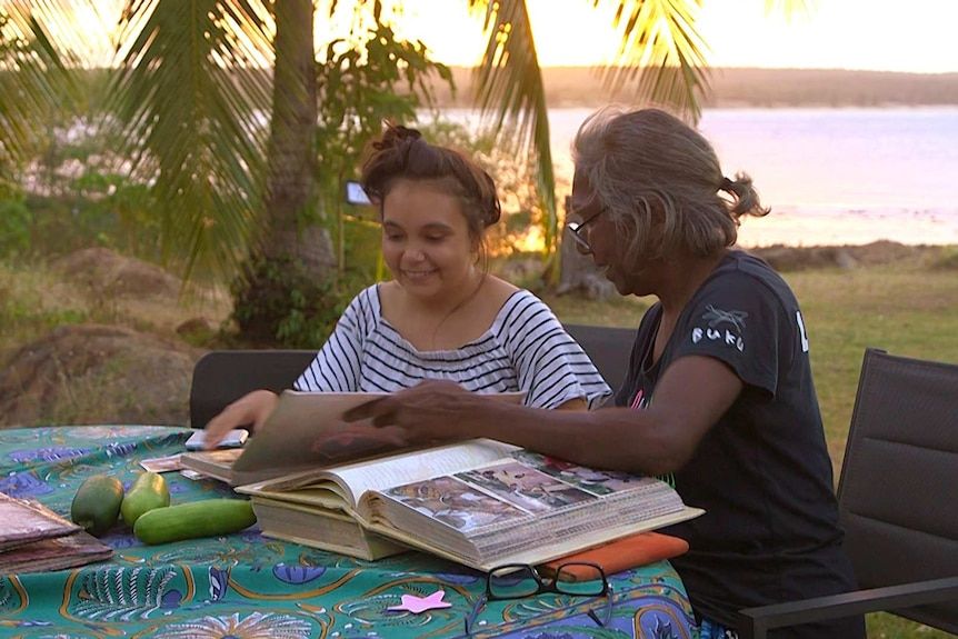 Young woman and mother sitting at table outside looking at photo albums at sunset.