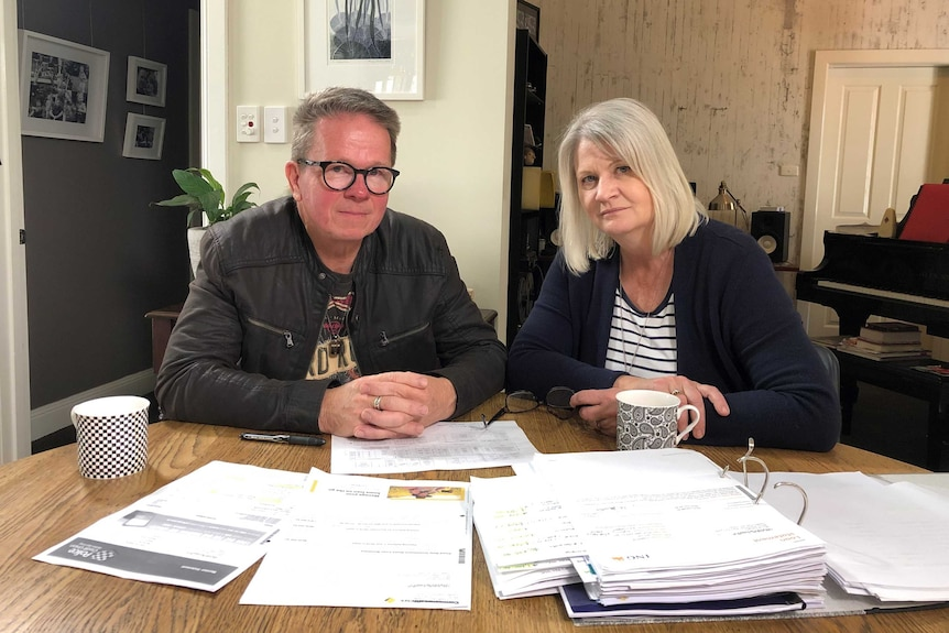 Peter and Bronwyn Dwight sitting at a table covered in folders and financial documents