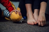 A woman's hand on her bare feet next to a child's hand on a toy.