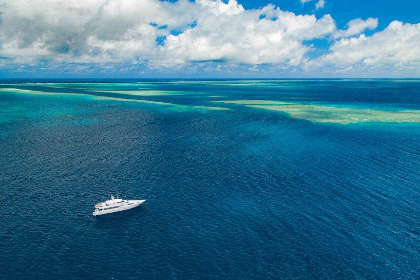 An aerial shot of a research ship in the Great Barrier Reef.