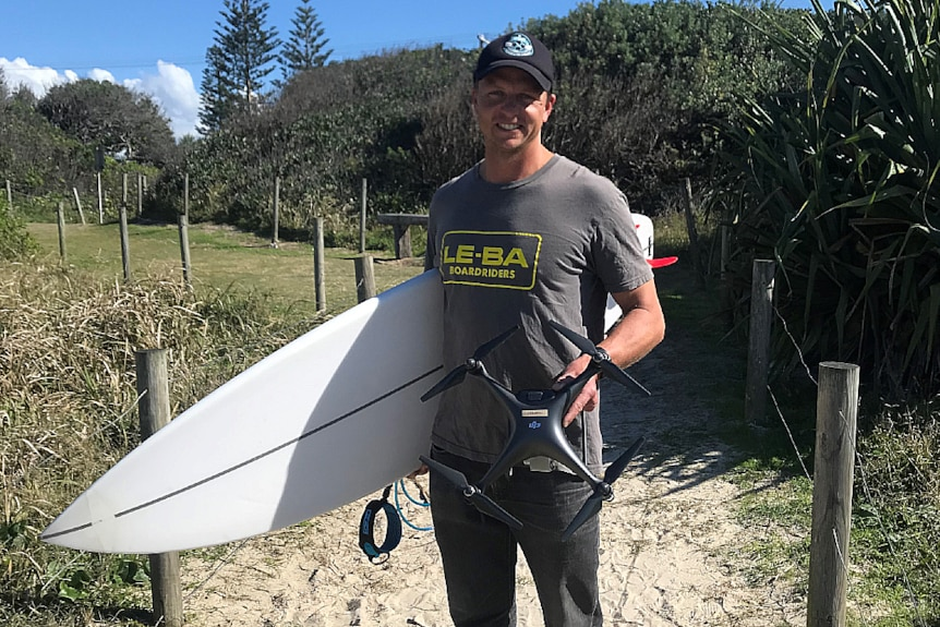 A man is holding a drone in one hand and a surfboard in the other