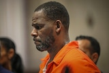 R kelly looking down whle in orange jumpsuit in court