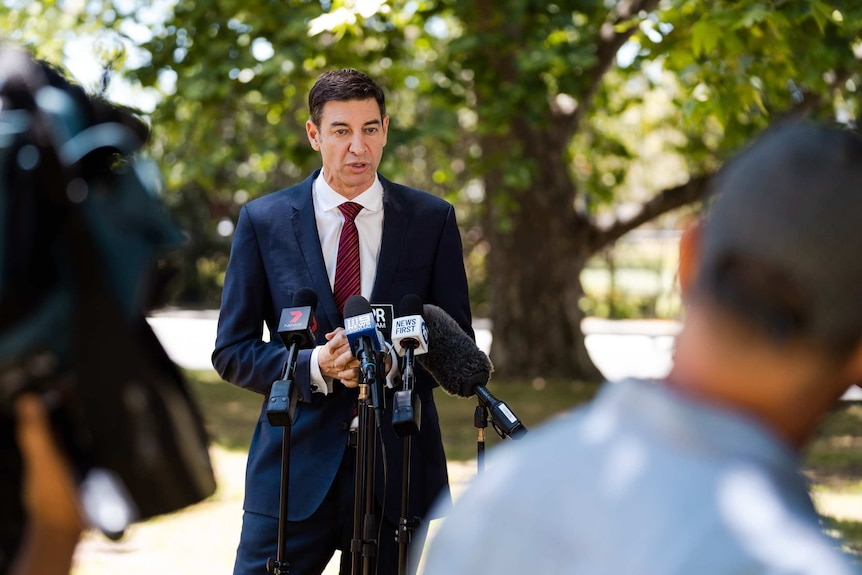 A man in a blue suit and a red tie speaks to the media while standing in a park.