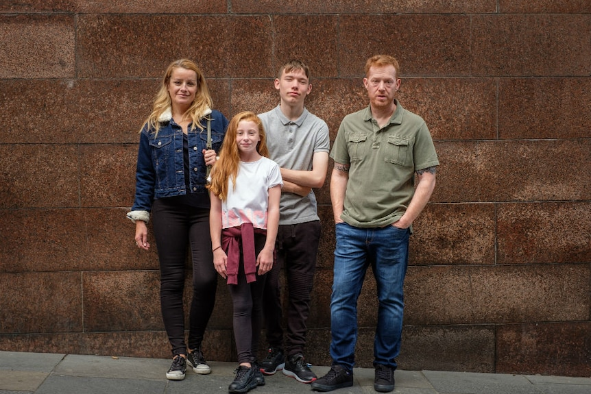 A woman, young girl, teenage boy, and man pose against an urban wall