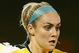 An Australian Matildas player dribbling the ball against Thailand.