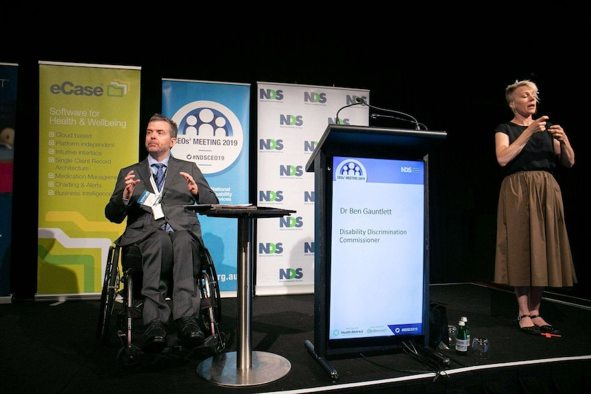 Dr Ben Gauntlett speaking on stage, he is in a wheel chair and there is a Auslan interpreter next to him for the audience.
