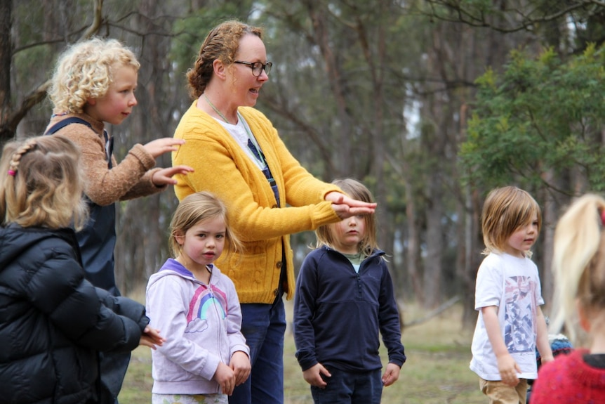 A school teacher stands with a group of primary school children in a bush setting
