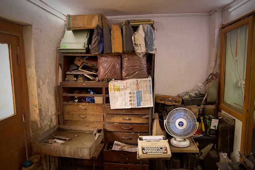 An old worn set of wooden drawers with shelved packed with bags and objects, in a small room