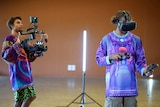 Young men using virtual reality technology including headgear and controllers.
