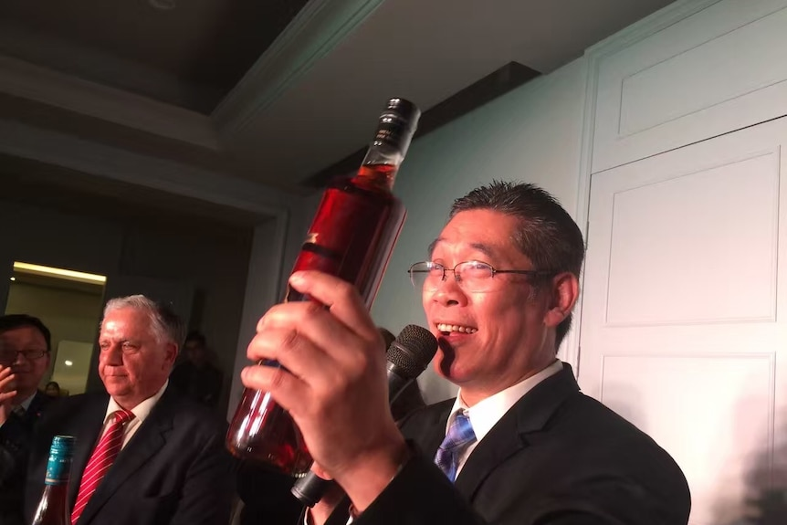 dr thomas tang holds up a bottle of wine while speaking to crowd