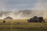 Dust rises over a field as soldiers and a tank move across it.