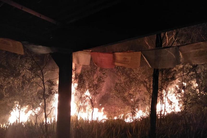 A bushfire burning close to a house at night