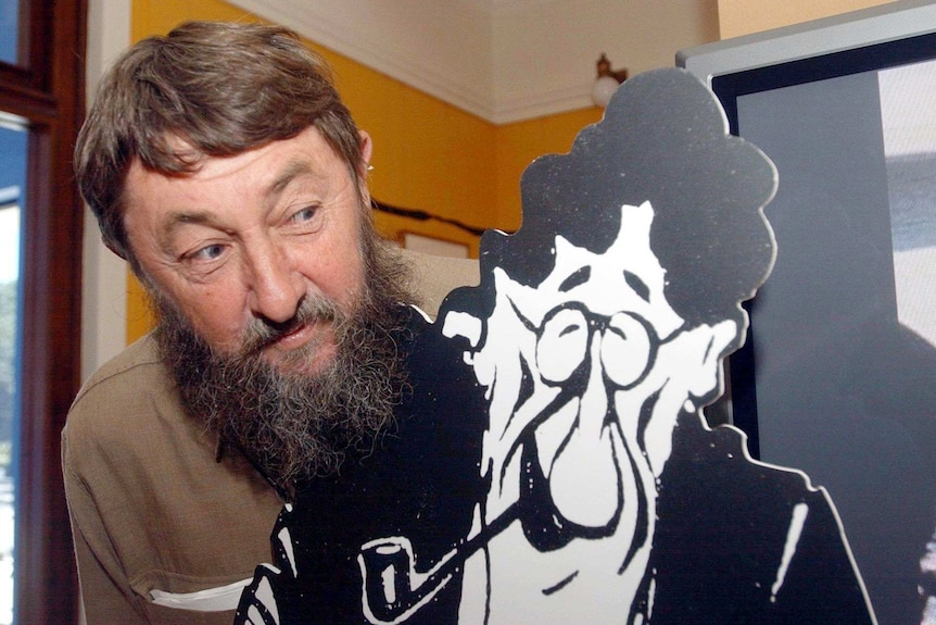 A man with a beard looks at a large cardboard cut-out.
