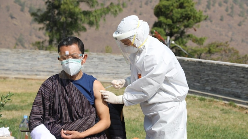 A man in traditional Bhutanese dress receiving an injection from a health worker in full PPE