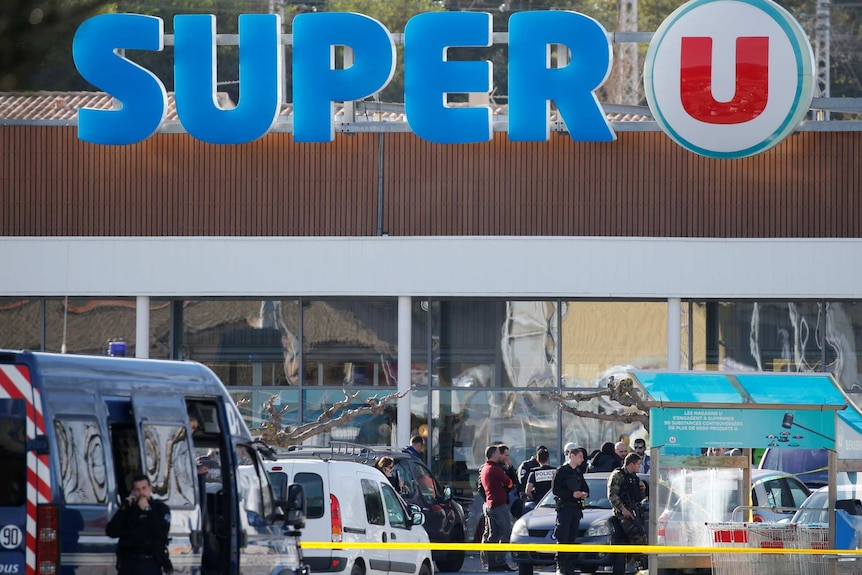 A general view shows gendarmes and police officers at a supermarket.
