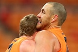 Two GWS Giants AFL players embrace as they celebrate beating Collingwood.