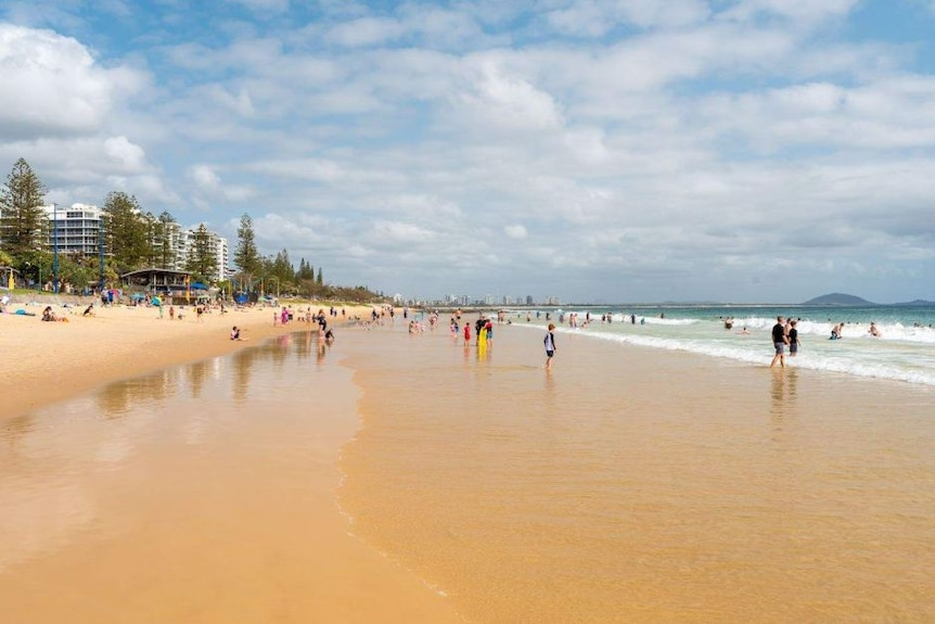 People walking along a beach at Mooloolaba in Queensland