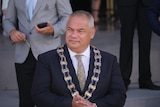 A man with short, grey hair wearing a dark suit and a mayoral ribbon around his neck.