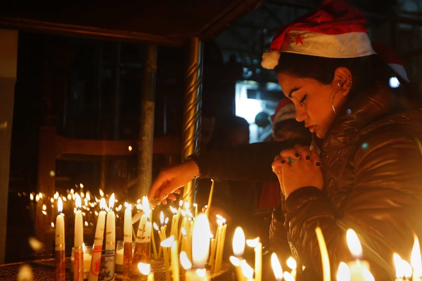 A woman prays before several candles.