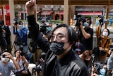 A masked man in a suit stands before a crowd of journalists and onlookers. He has raised his fist above his head