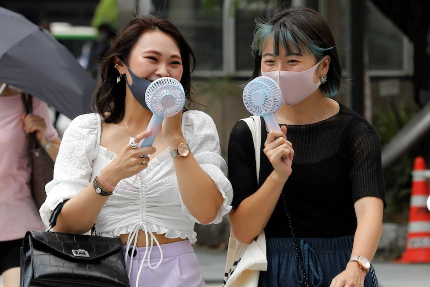 Two women wearing masks blow fans on their faces as they walk