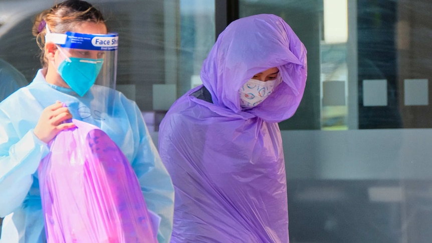 A woman swaddled in plastic and another woman in full PPF holding a full plastic bag.