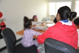 Broken Hill woman Delenna King sits with her back to the camera and her face obscured, with two children at a table, blurred out