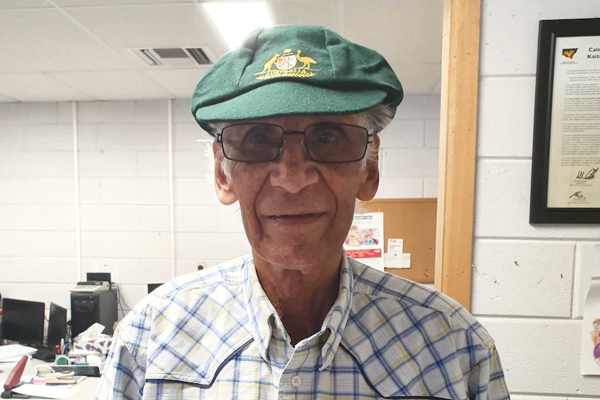 A man in a baggy green cap looks at the camera.
