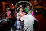 Volunteers help an injured person onto a cart.