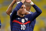 Kylian Mbappe applauds the French fans