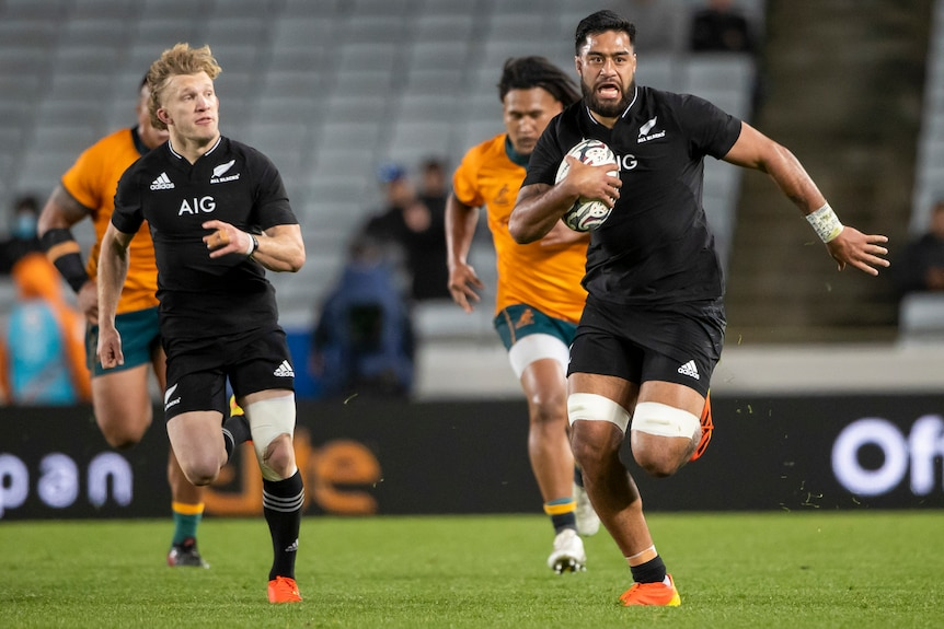 A New Zealand player runs free with a teammate on his shoulder as the Wallabies are left behind.