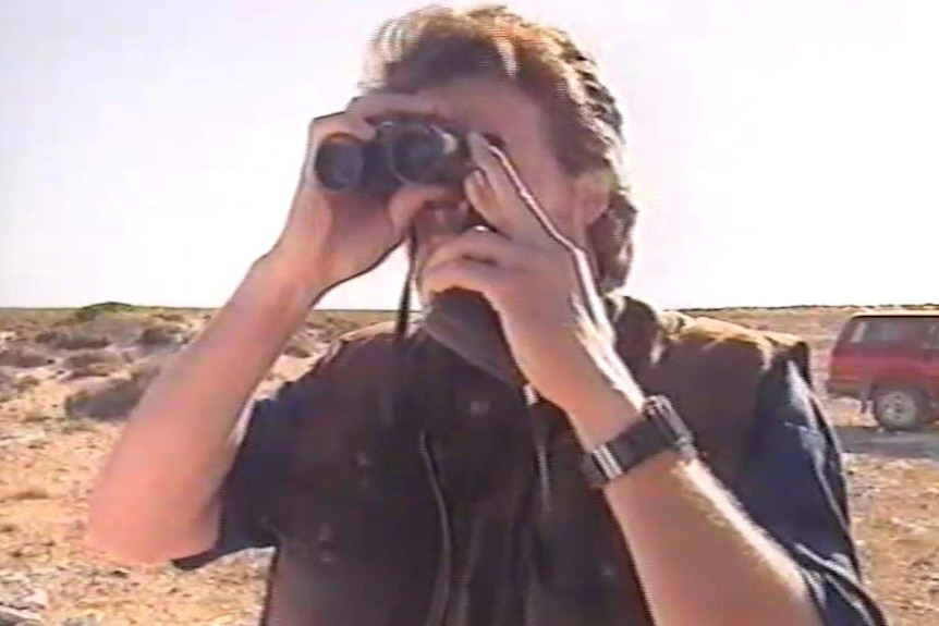 A man stands on what appears to be the top of a cliff, looking through a pair of binoculars.
