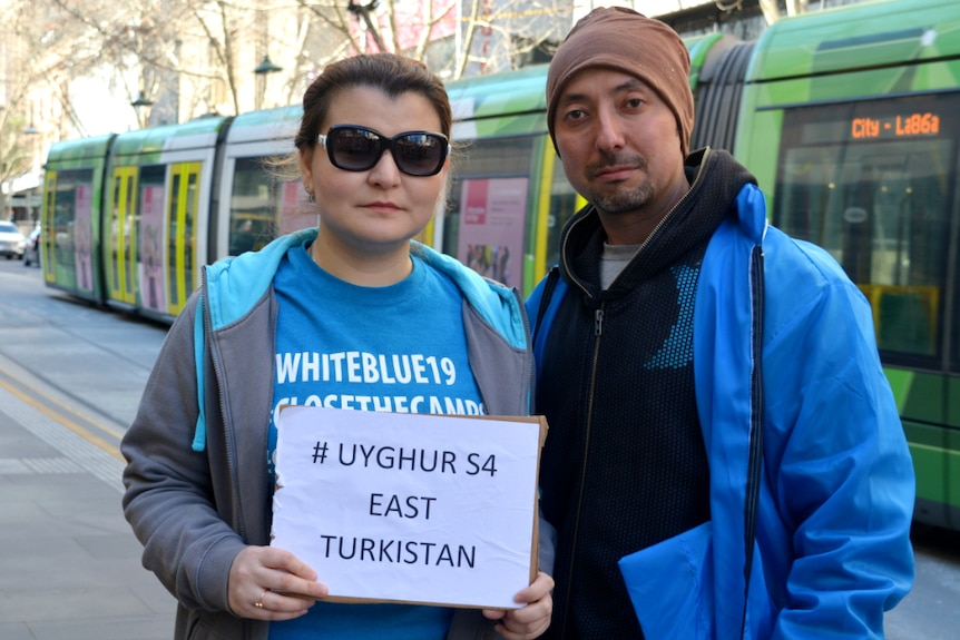 A Uyghur couple wearing bright blue jackets stand in front of a green Melbourne tram.
