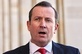 WA Premier Mark McGowan, speaking at a press conference outside parliament, mouth open, mid speaking